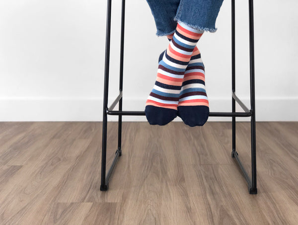 woman's feet on bar stool with coral and blue striped compression socks