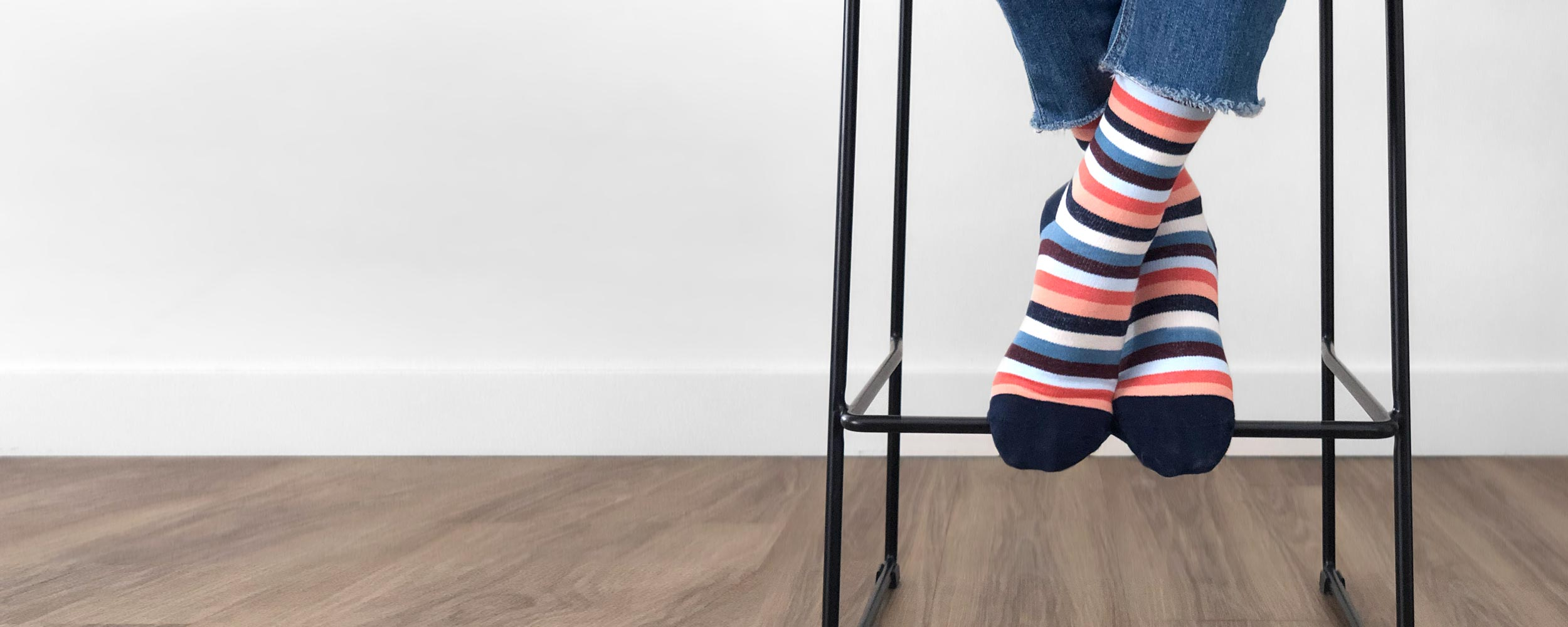 Woman's feet on bar stool wearing coral and blue striped compression socks