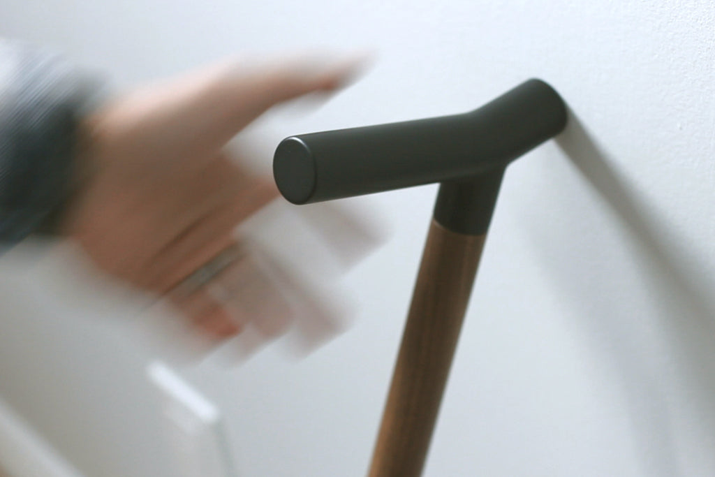 Hand reaching for cane handle