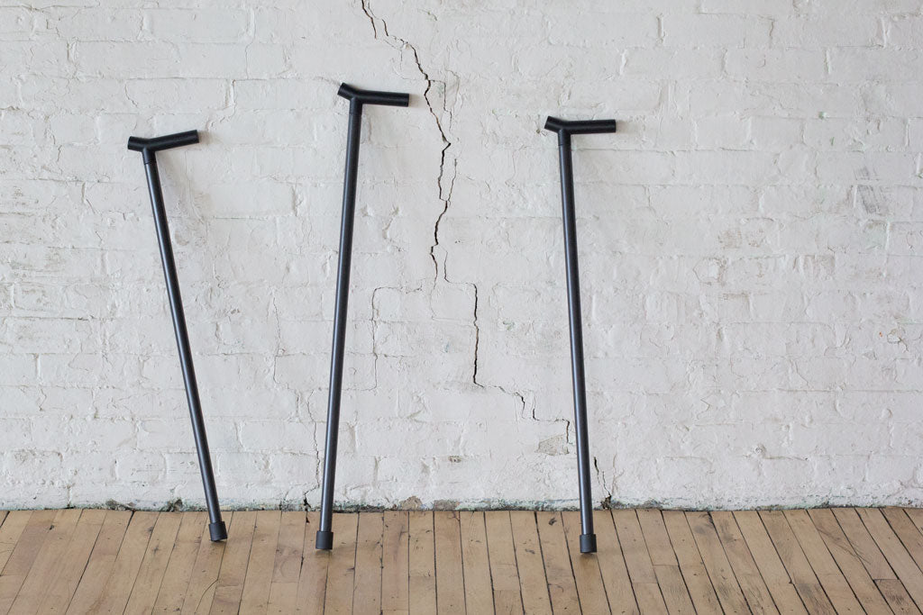 three carbon fibre walking sticks leaning on a wall