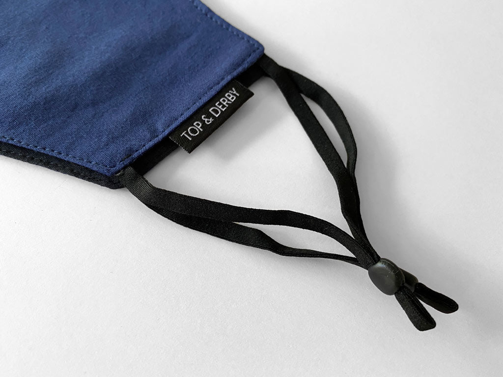 close detail view showing blue cotton face mask with logo tag