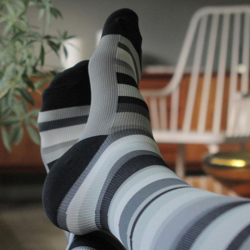 Feet resting with black, grey and white striped pattern compression socks
