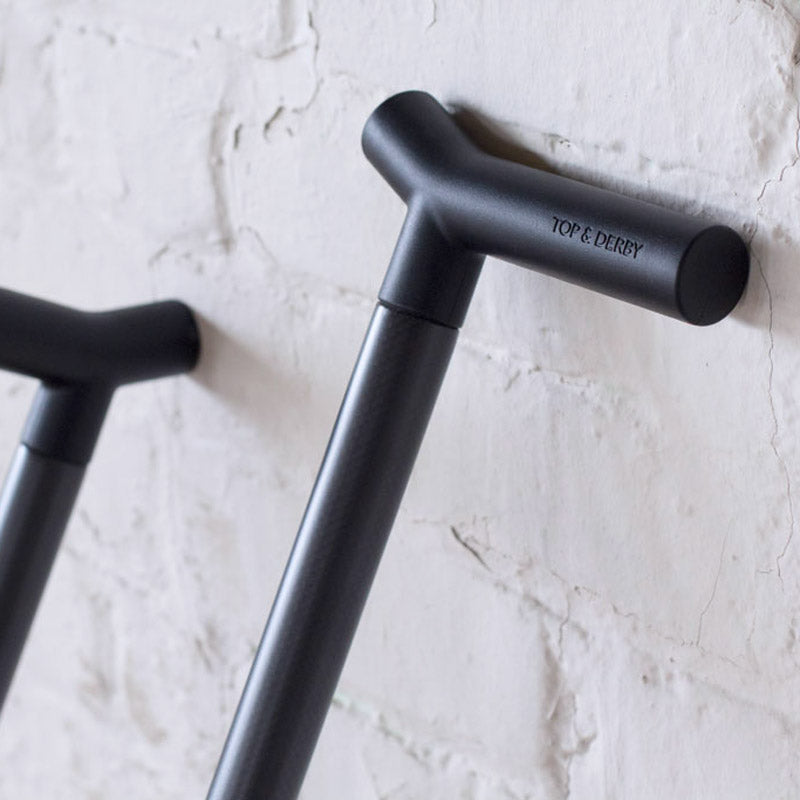 Two black CFX carbon fiber Top & Derby walking sticks leaning on brick wall