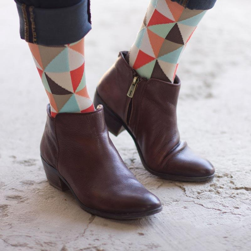 Woman's feet wearing coral cream triangle pattern energy compression socks with brown low brown boots