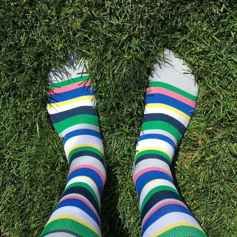 Feet in grass with patterned surgical compression stockings in grey, green and blue