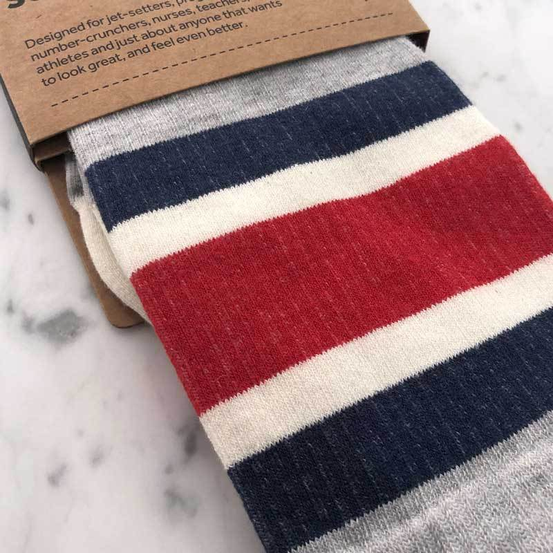 Close detail of sport stripe pattern compression socks in heather grey, blue and red