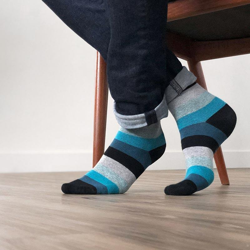 Man's feet sitting in chair with blue and black striped compression socks