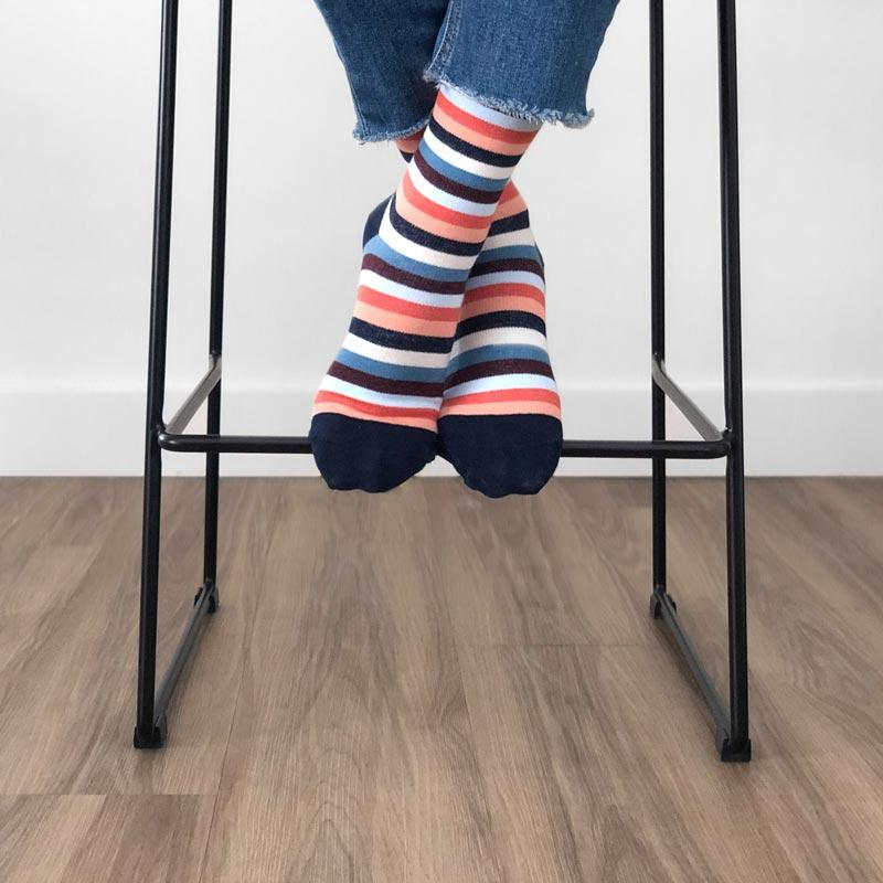 Woman's feet on bar stool wearing stripe patterned compression sock in shades of coral, navy and cream