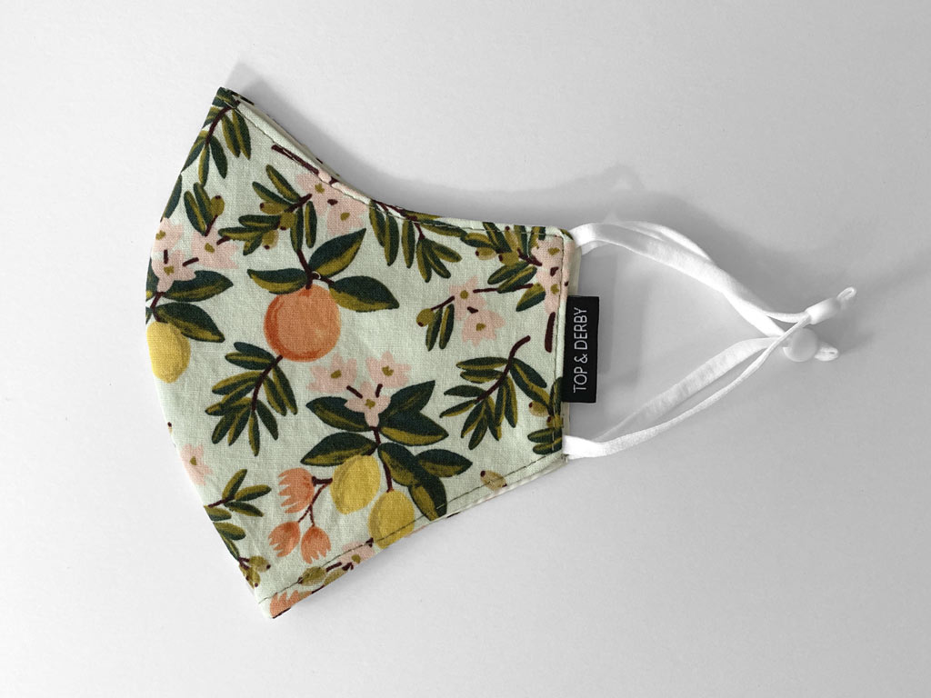 side view of mint cotton face mask with citrus flower print
