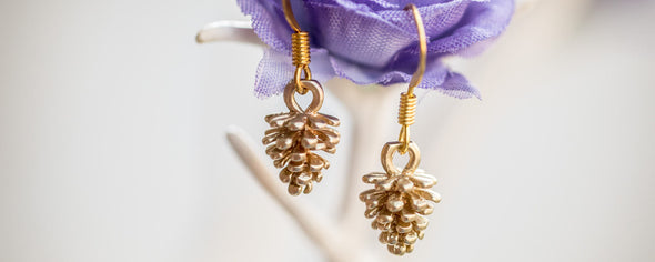 tini tiny gold pine corn earings on hanging a purple flower