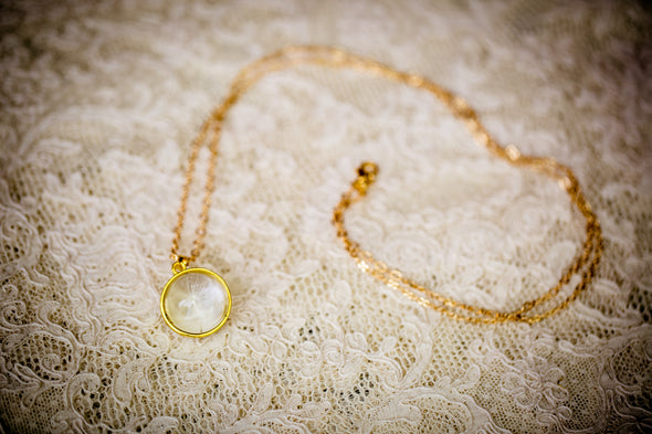 Gold plate dandelion seed necklace with a single seed lying on lace