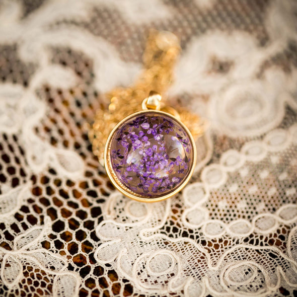 purple dried flower orb silver necklace on lace background