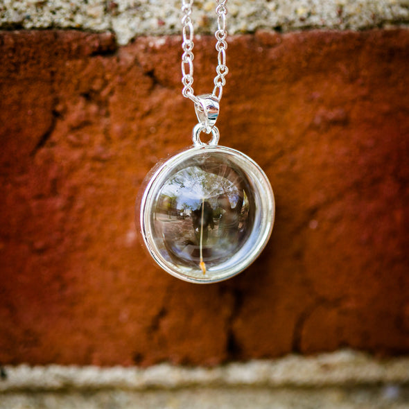 sterling silver dandelion seed necklace with single seed, red brick background