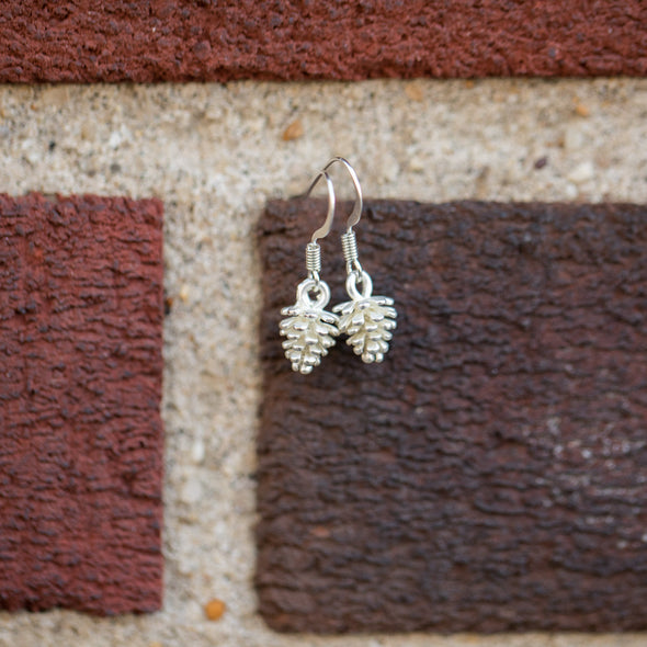 tiny silver pine corn earrings hanging on brick wall