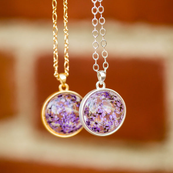 purple dried flower orb silver necklace hanging with brick wall background