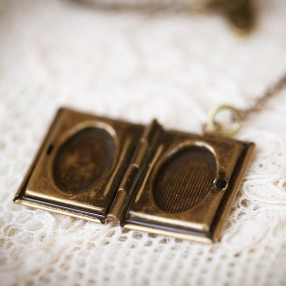 literature book locket lying closed on lace