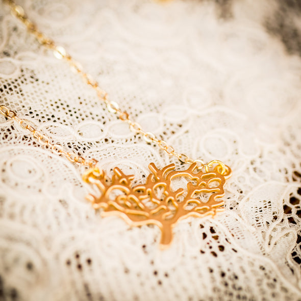 The Kamali small gold necklace on lace (close-up)