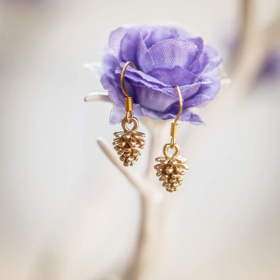 tiny gold pine corn earrings hanging on a purple flower