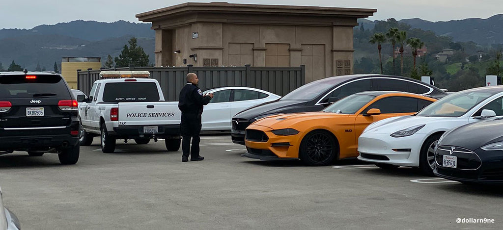 Ford Mustang blocking the Tesla Supercharger, a cop with the tow truck is on-site to tow the ICE car away.