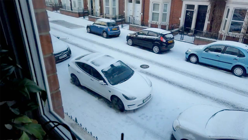 Tesla Model 3 melting snow via Tesla phone app remotely while other cars stare enviously.