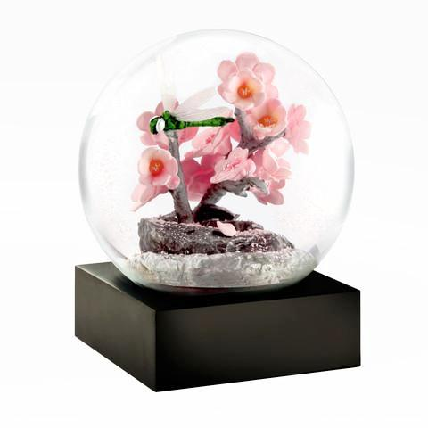 dragonfly sits on pretty pastel pink flowers in this snow globe