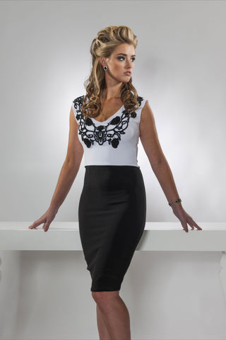 This is a black and white v-neck cocktail dress with black applique