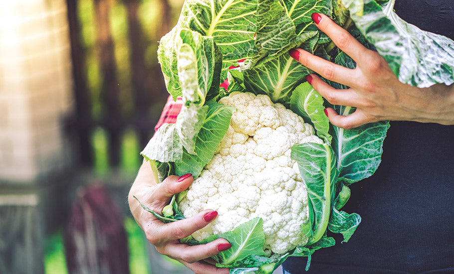 woman holding whole cauliflower