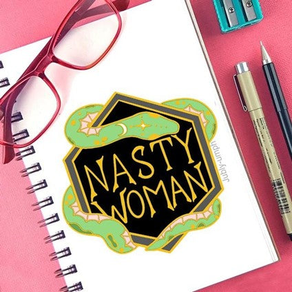 Notepad on table with a drawing of a shield, encircled by a snake, with the words 'Nasty Woman' on it.  The notebook is surrounded by reading glasses, pens and pencils, and a pencil sharpener