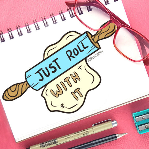 Print of a rolling pin with 'just roll with it' written on it