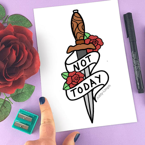 flatlay image with a rose and a pen and a hand holding the corners of a page. the page is a drawing of a dagger with a banner that reads 'not today'. the