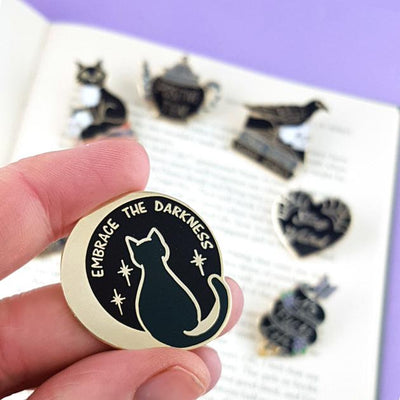 "hand holding a round pin with a cat sitting on a moon that reads ""Embrace the darkness"". In the background but blurry are the shapes of 5 other black coloured pins."