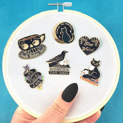 6 'Black' themed enamel lapel pins, pinned on an embroidery hoop, held by a woman's hand with black painted nails.