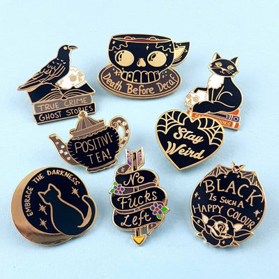 "8 enamel pins with black enamel and gold metal. the pins are ""Death Before Decaf"", ""cats and books"", ""stay weird "", ""black is such a happy colour"" ""no fucks left"" ""Embrace the darkness, ""positivi-tea"" ""true crime and ghost stories"""