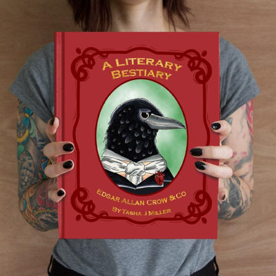 A person with tattooed arms holds a copy of A literary bestiary Book by Tasha J Miller. The book has a red cover and a picture of  crow