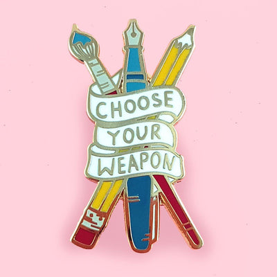 Enamel lapel pin depicting a red paintbrush, a blue fountain pen, and a yellow pencil, all crossed over each other and wrapped in a banner that displays the words 'Choose Your Weapon'.