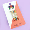 Enamel lapel pin depicting a red paintbrush, a blue fountain pen, and a yellow pencil, all crossed over each other and wrapped in a banner that displays the words 'Choose Your Weapon'. It's pinned to a business card-sized pink and white Jubly-Umph lapel pin card.