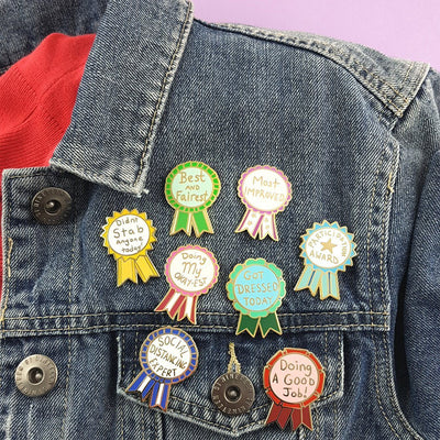 "a blue denim jacket with a collection of pins attached. The top pin reads ""Best and Fairest"""