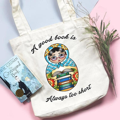 "flatlay image of a White canvas tote bag featuring an image of a matryoshka doll with books and text that reads ""A good book is always too short"", there is a book and a bunch of leaves on either side of the tote bag"