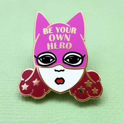 "An enamel pin with a picture of a white woman with brown hair and a purple superhero hat. it says ""Be  your own hero"" on the hat"