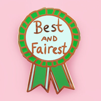 "An enamel pin in the shape of an award ribbon. The ribbon is green on the ouside with mint green in the middle and has text that reads ""Best and Fairest"""