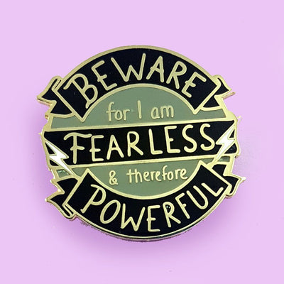 round black and grey enamel lapel pin with the words beware for I am fearless and powerful on it, with two small lightning bolts.