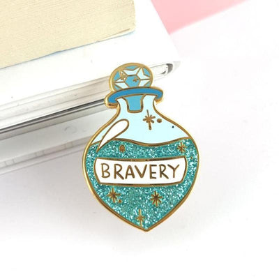 Vintage potion bottle shaped lapel pin, with a round crystal stopper, with blue glittery liquid inside, and the word 'Bravery' on a label on the front, positioned sitting against the corner of a writing pad..
