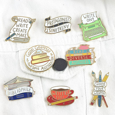 Group of 8 pro-creative writing themed lapel pins, pinned on the pocket of a white corduroy jacket.