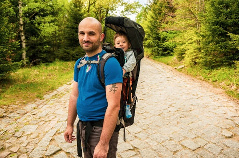 Dad carrying toddler in backpack carrier