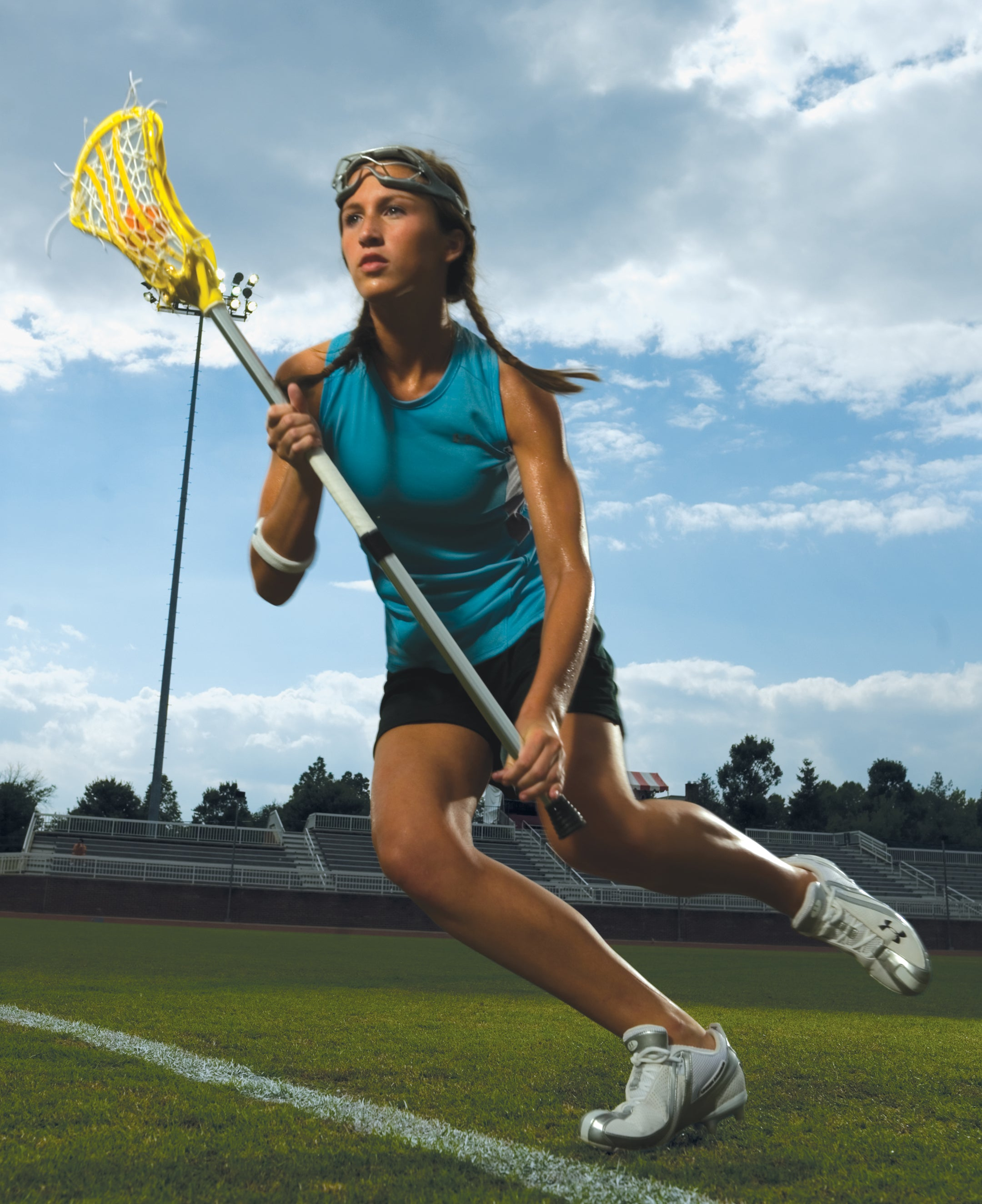 Girl playing lacrosse with complete lacrosse stick and full equipment in Edmonton, Canada.