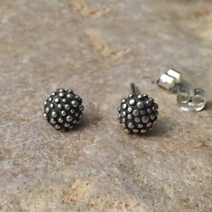 sterling silver ear studs textured with raised dots over a small domed pillow