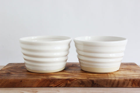 White ceramic snack bowls and olive wood cheese board