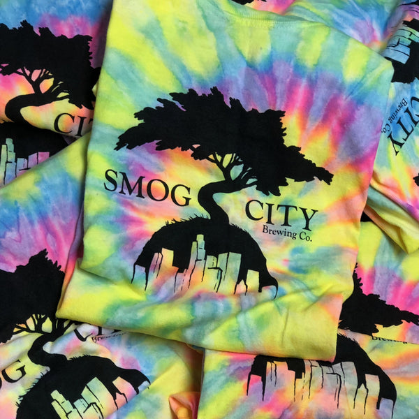 Smog City logo tie dye shirts in staggered pile.