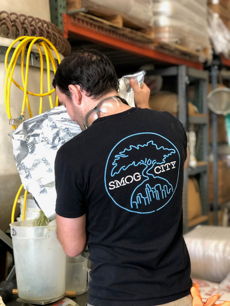 The back of a brewer wearing the black and neon pocket T is weighing hops.