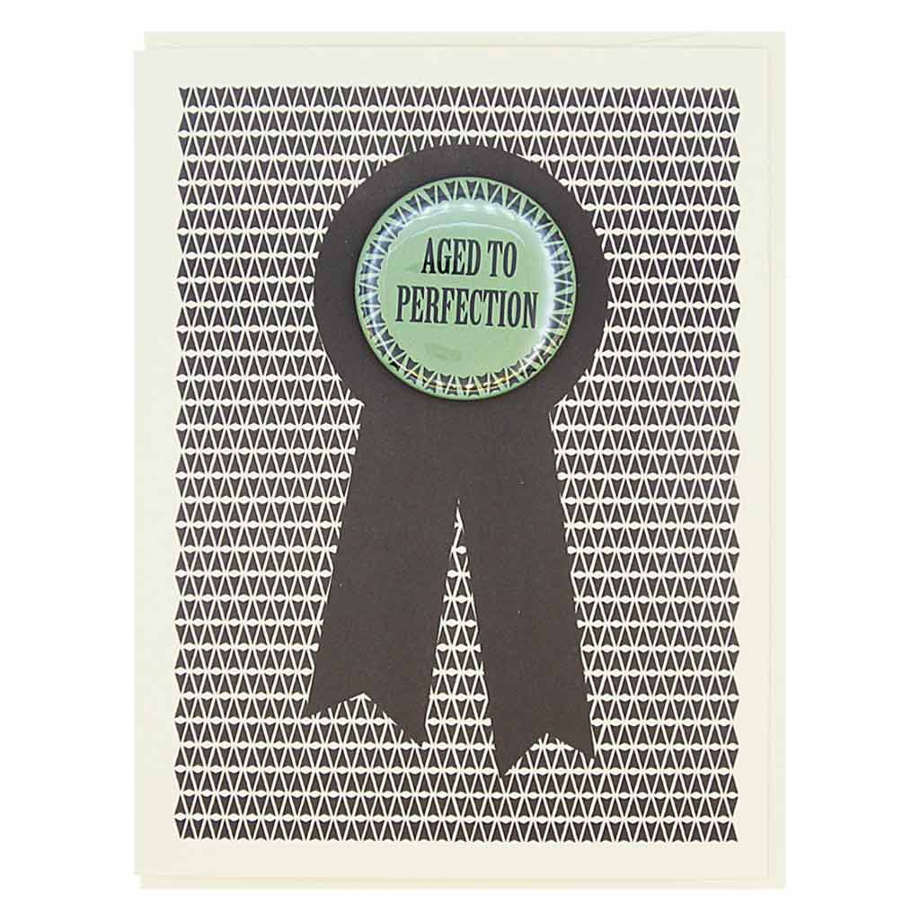 "This birthday card looks like a prize ribbon. Features a 1½"" button with the text 'Aged to Perfection' that can be taken off and proudly worn by the recipient. Card measures 4¼"" x 5½"", comes with a cream envelope & is blank inside."